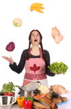 Housewife juggling with fruit and vegetables Stock Photography