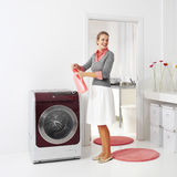 Housewife keeps detergent. Near the washing machine in laundry room Royalty Free Stock Image