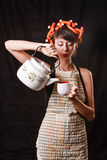 Housewife with a kettle and a cup Stock Photography