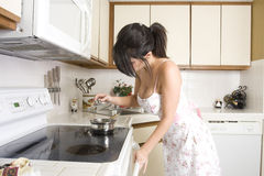 Housewife in the kitchen. Beautiful brunette housewife working in her kitchen Royalty Free Stock Photography