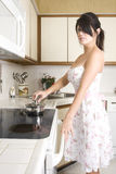 Housewife in the kitchen. Beautiful brunette housewife working in her kitchen Stock Photography