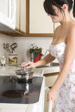 Housewife in the kitchen. Beautiful brunette housewife working in her kitchen Royalty Free Stock Photo