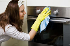 Housewife in the kitchen. Cleaning the oven in the kitchen Royalty Free Stock Photos
