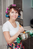 Housewife in the kitchen. Housewife in apron and curler with the pot or saucepan and potato masher in the kitchen Royalty Free Stock Photo