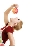 Housewife in kitchen apron eating apple healthy fruit Royalty Free Stock Photography