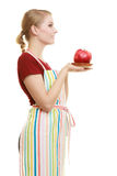 Housewife in kitchen apron offering apple healthy fruit. Diet and nutrition. Blonde young housewife or chef in striped kitchen apron offering red apple healthy Royalty Free Stock Images