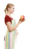 Housewife in kitchen apron offering apple healthy fruit. Diet and nutrition. Blonde young housewife or chef in striped kitchen apron offering red apple healthy Stock Photo