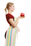 Housewife in kitchen apron offering apple healthy fruit. Diet and nutrition. Blonde young housewife or chef in striped kitchen apron offering red apple healthy Stock Photography