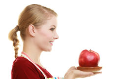 Housewife in kitchen apron offering apple healthy fruit. Diet and nutrition. Blonde young housewife or chef in striped kitchen apron offering red apple healthy Stock Images