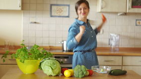 A housewife in the kitchen is in a good mood. She cuts vegetables and sings with a carrot as if she were a microphone. stock footage