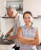 Housewife at kitchen and her husband washing plates Stock Images