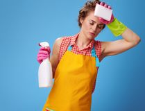 Housewife with kitchen sponge and bottle of detergent on blue Stock Images