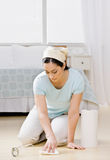 Housewife kneeling in bedroom wiping up spill. Ed water with paper towel Stock Photo