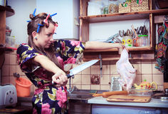 Housewife with knife and carcass of a hen in hands Royalty Free Stock Image