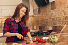 Housewife with a knife cutting vegetable in the kitchen Stock Photography