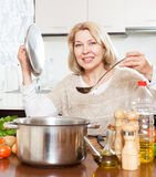 Housewife  with ladle cooking soup in pan  in home kitchen Royalty Free Stock Images