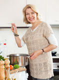 Housewife  with ladle cooking soup in pan at   kitchen  interior Royalty Free Stock Photos