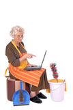 Housewife on laptop. Middle aged housewife with curlers in hair planning household on laptop. House cleaning utensils on the side Stock Photography