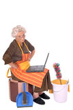 Housewife on laptop. Middle aged housewife with curlers in hair planning household on laptop. House cleaning utensils on the side Stock Photos