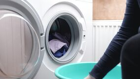 Housewife loads clothes from Laundry basket into a washing machine
