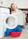 Housewife looking at  clothes near washing machine Stock Photography