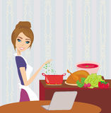 Housewife looking in laptop during cooking soup Stock Photos