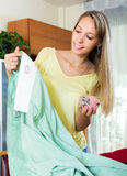 Housewife looking at new curtains Royalty Free Stock Images