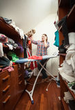 Housewife looking at not ironed clothes at wardrob Royalty Free Stock Photography