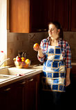Housewife looking at orange on country styled kitchen Royalty Free Stock Photos