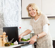 Housewife looking recipe  for cooking  in the internet  at home's kitchen Stock Images