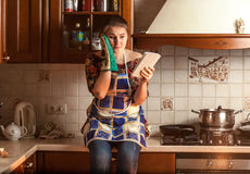 Housewife looking recipe on tablet while sitting on tabletop Royalty Free Stock Photo