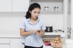 Housewife looking smartphone in kitchen Royalty Free Stock Photos
