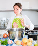 Housewife looking at spoiled food in pan Royalty Free Stock Photo