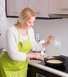 Housewife making omlet Royalty Free Stock Photo