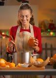 Housewife making orange jam in  in kitchen. Happy young housewife making orange jam in christmas decorated kitchen Stock Photo