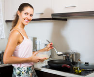 Housewife making pancakes on pan Royalty Free Stock Images