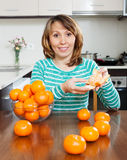Housewife with mandarins at  kitchen Royalty Free Stock Photo