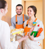 Housewife meeting cleaning crew at doorway Royalty Free Stock Images