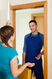 Housewife meeting fixing worker at the door at home royalty free stock photo