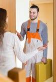 Housewife meeting workman. At apartment doorway Royalty Free Stock Photo