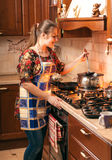 Housewife mixing soup with soup ladle in saucepan Royalty Free Stock Images