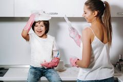 Free Housewife Mom In Pink Gloves Washes Dishes With Her Son By Hand In The Sink With Detergent. A Girl In White And A Child With A Royalty Free Stock Images - 187229639