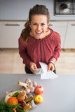 Housewife with money and grocery shopping checks Stock Photos