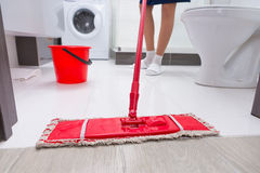 Housewife mopping the floor in a bathroom. With a low angle close up view of a colorful red mop and her feet behind Stock Images