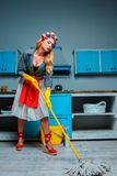 Housewife mopping floor. Beautiful upset housewife mopping floor in kitchen Royalty Free Stock Photos