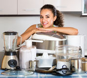 Housewife with multicooker and appliances. Happy housewife with multicooker and other culinary appliances at home Royalty Free Stock Photo