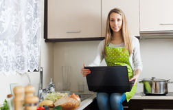 Housewife with notebook in home kitchen Royalty Free Stock Photography