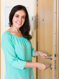 Housewife open new lock of door. Smiling housewife trying new lock of front door royalty free stock image