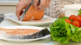 Housewife pensioner prepares dietary dinner. Grilled trout on a pair and vegetable garnish. stock video footage
