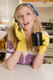 Housewife on the phone. Blond caucasian woman wearing yellow cleaning gloves and bandana holding a cup of coffee talking on phone while leaning on a kitchen royalty free stock images
